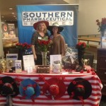 Terri Payne and Tess Davis rocking their derby hats and roses at the Southern Pharmaceutical Services booth.